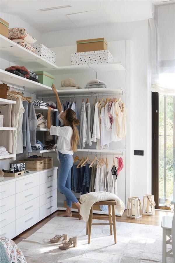 organizar armario vestidor mujer cogiendo caja ropa perchas 3ee83cff 600x900 - La felicitat en l'ordre segons Marie Kondo